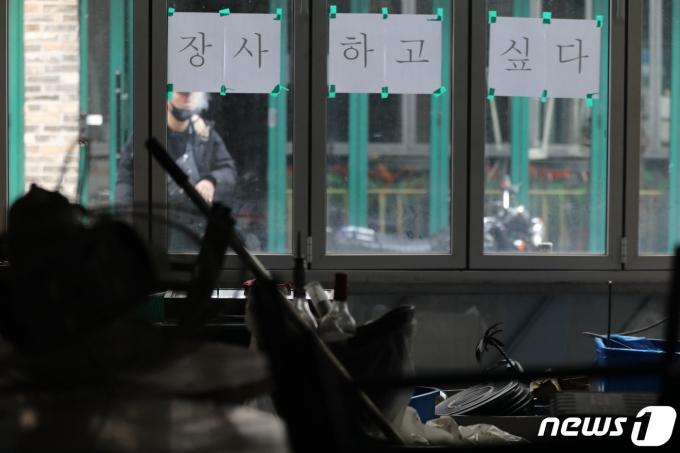 소상공인 버팀목자금(3차 재난지원금) 지급 사흘째인 14일 오후 서울 용산구 이태원 거리에 신종 코로나바이러스 감염증(코로나19) 타격으로 사실상 폐업절차를 밟고 있는 한 가게에 '장사하고 싶다' 글귀가 붙어 있다. (사진은 촬영 후 좌우 반전) 2021.1.14/뉴스1 © News1 이동해 기자