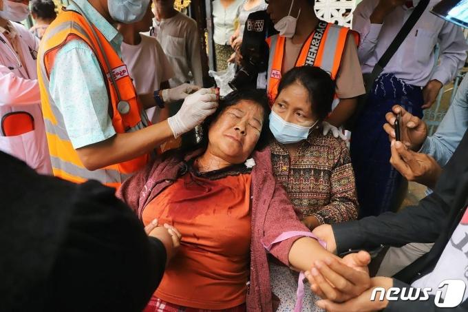 20일(현지시간) 미얀마 만달레이에서 군사 쿠데타를 규탄하는 시위대가 군경의 폭행으로 다친 머리를 의료진의 치료를 받고 있다. © AFP=뉴스1 © News1 우동명 기자