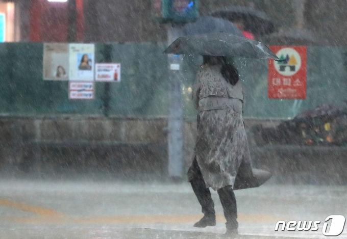 지난해 5월18일 오후 서울 광화문네거리에서 시민들이 갑자기 내린 폭우에 발걸음을 옮기고 있다. 2020.5.18/뉴스1 © News1 구윤성 기자