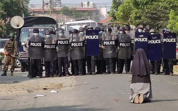 안 로사 누 타웅 수녀가 무장한 경찰들 앞에 무릎을 꿇고 시위대에 사격을 하지 말아달라고 호소하고 있다. (찰스 마웅 보 추기경 트위터 갈무리/뉴스1)
