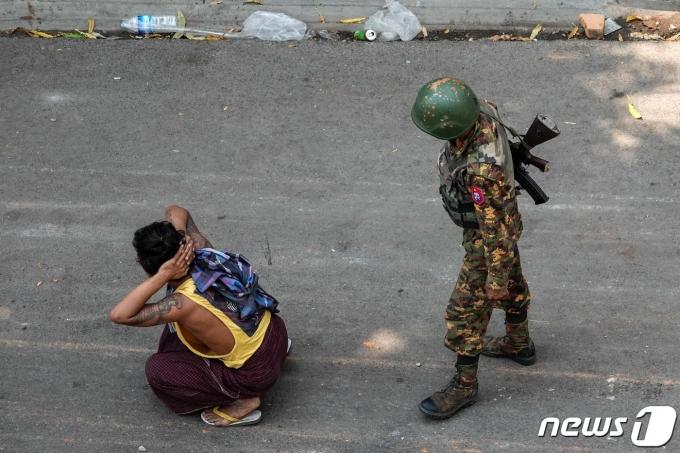 3일 미얀마 군인이 반쿠데타 시위자의 뒤에 서 있다. © AFP=뉴스1