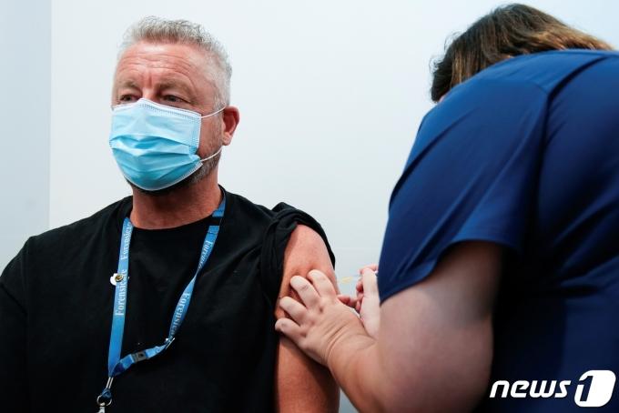 호주에서 한 의료진이 코로나19 백신을 접종하고 있다. © 로이터=뉴스1