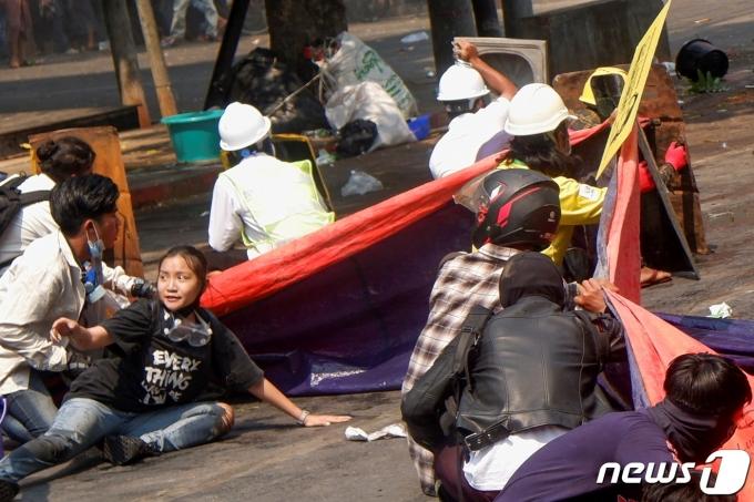 미얀마 '19세 태권소녀'로 알려진 故 치알 신이 2021년 3월 3일 미얀마 만달레이에서 시위 도중 뒷사람에게 엎드려 몸을 피하라며 챙기는 모습이 카메라에 포착됐다. © 로이터=뉴스1 © News1 최서윤 기자