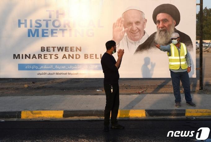 이라크 나자프에서 2021년 3월 3일 프란치스코 교황의 방문을 앞두고 교황과 아야톨라 알리 알시스타니 시아파 최고성직자의 모습이 담긴 포스터가 전시된 모습. © 로이터=뉴스1 © News1 최서윤 기자
