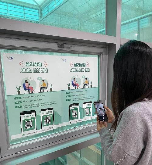 한 주민이 복지시설에 붙은 포스터의 QR코드를 찍고 있다./사진제공=강북구