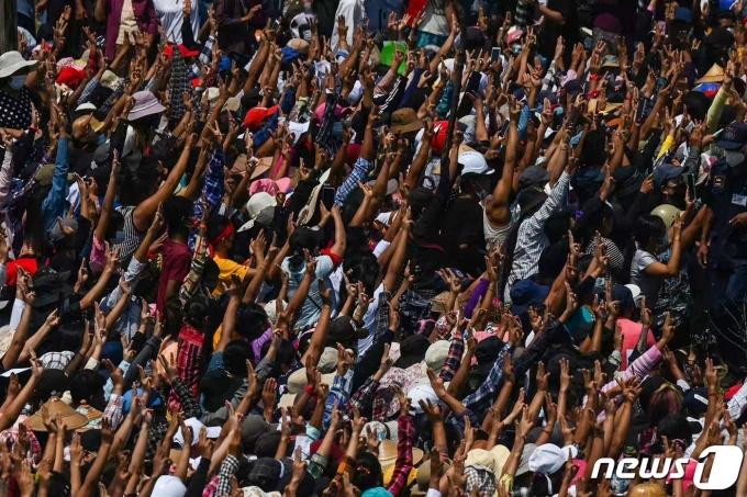 2일(현지시간) 미얀마 양곤에서 군부 쿠데타 규탄 시위 중 군경의 총을 맞고 숨진 니 니 아웅 뗏 나잉의 장례식서 시민들이 '세 손가락 경례'를 하며 추모하고 있다. © AFP=뉴스1 © News1 우동명 기자