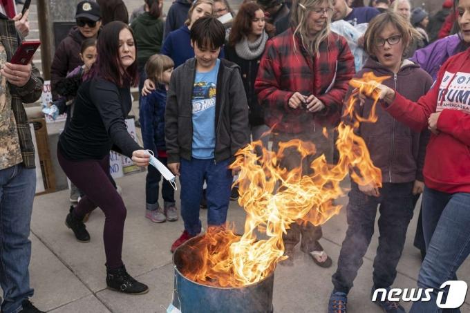 미국 아이다호주에서 마스크 착용 의무화 조치에 반대하는 시위대가 마스크 화형식을 벌였다. © AFP=뉴스1