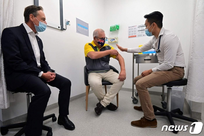 코로나19 백신을 맞고 있는 스콧 모리슨 호주 총리(가운데)와 그렉 헌트 보건장관(왼쪽). © AFP=뉴스1