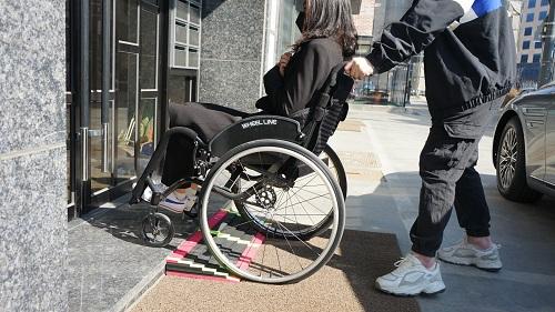 한 휠체어 이용자가 시설에 설치한 이동식 경사로를 이용하고 있다./사진제공=서울시