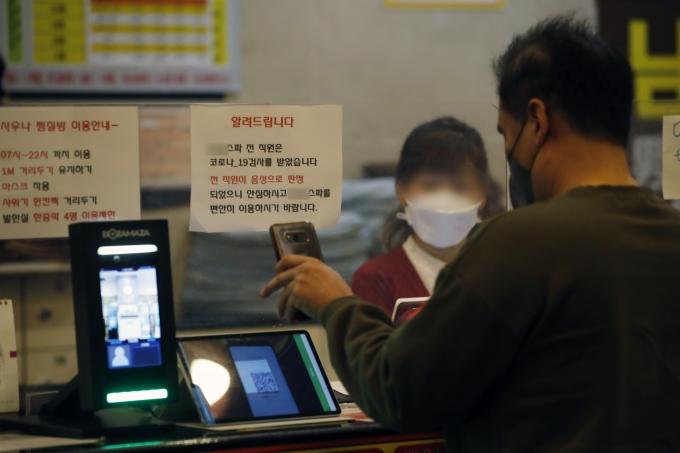 오늘부터 모든 다중이용시설 이용자는 빠짐없이 출입 명부를 작성해야 한다. 사진은 지난 22일 서울 시내의 한 목욕탕 카운터에서 한 시민이 QR코드를 인식하고 있는 모습. /사진=뉴스1