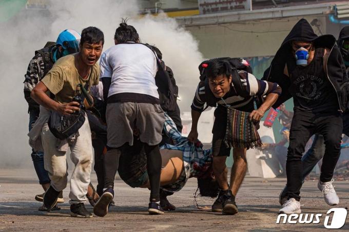 17일(현지시간) 미얀마 양곤에서 군사 쿠데타를 규탄하는 시위 중 실탄에 맞아 부상을 당한 시민을 시위대가 옮기고 있다. © AFP=뉴스1 © News1 우동명 기자