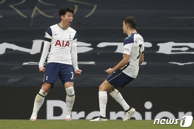 손흥민이 12일(한국시각) 영국 런던 토트넘 홋스퍼 스타디움에서 열린 맨체스터 유나이티드와의 2020-21 잉글랜드 프리미어리그(EPL) 31라운드 경기 전반전에서 선제골을 넣은 뒤 팀동료 세르히오 레길론에게 축하를 받고 있다. © AFP=뉴스1