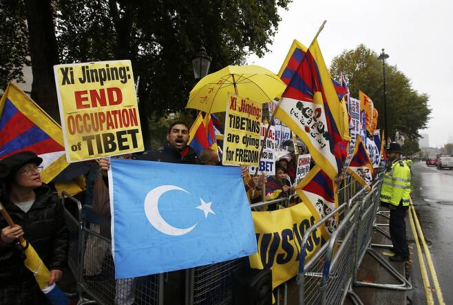 영국 런던 중심가 다우닝가에서 한 남성이 친티베트 지지자들 사이에서 위구르 깃발을 흔들며 시진핑 중국 국가주석 반대 시위를 벌이고 있다. / 사진=로이터