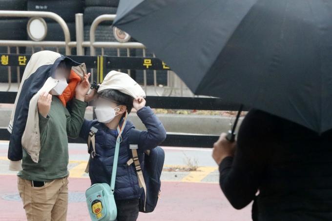 17일 토요일은 중부지방을 중심으로 곳곳에 소나기가 내린다. 사진은 지난해 11월17일  경기도 오산 시내에서 초등학생들이 소나기가 내리자 옷과 가방을 머리에 쓴 채 비를 피하는 모습. /사진=뉴스1