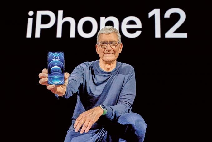 지난해 10월 미국 캘리포니아 쿠퍼티노에 있는 애플파크에서 팀 쿡 애플 CEO가 아이폰12를 들고 포즈를 취하고 있다. /사진=로이터