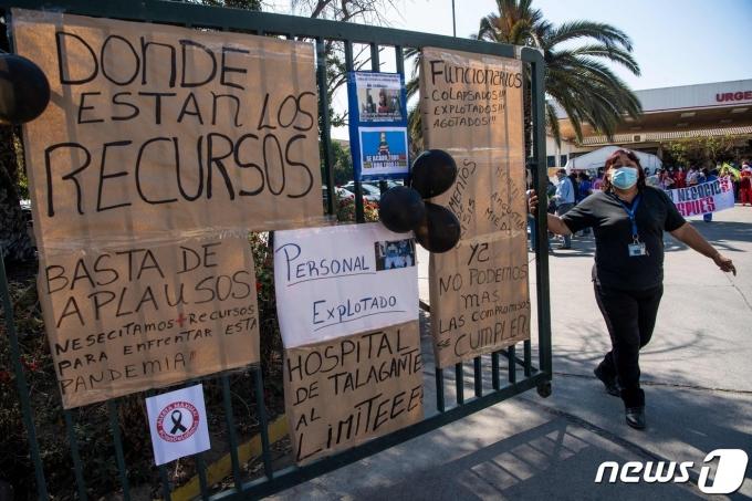 칠레 탈라간테의 한 종합병원 입구에 2021년 4월 15일 코로나19 감염 증가로 인한 자원 부족과 보건시스템 포화 상태에 항의하는 포스터가 붙어있는 모습. 칠레는 현재 중환자실 병상 점유율이 97%로 사상 최대치를 기록하는 등 보건시스템 붕괴 위기에 처했다. © AFP=뉴스1