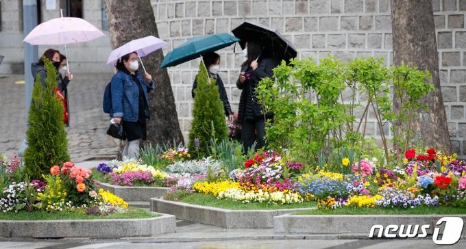 전국 곳곳에 비가 내린 16일 오후 서울 중구 덕수궁 앞에서 우산을 쓴 시민들이 지나가고 있다. 2021.4.16/뉴스1 © News1 안은나 기자