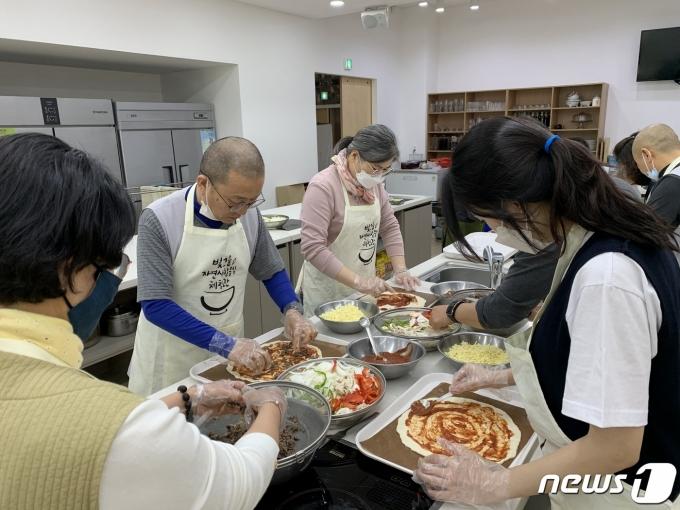 광주 증심사 주지 중현스님이 신도들과 함께 불우청소년들에게 전달할 피자를 요리하고 있다. (제공 자비신행회)© 뉴스1