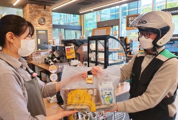 이마트24 매장에서 배달원이 다람이 봉투에 담긴 상품을 건네받고 있다. /사진=이마트24