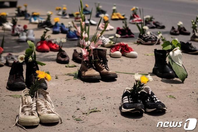 2021년 4월8일(현지시간) 미얀마 만달레이에서 군사 쿠데타를 반대하는 시위 중 꽃을 꽂아놓은 신발이 거리에 펼쳐져 있다. © AFP=뉴스1 © News1 우동명 기자