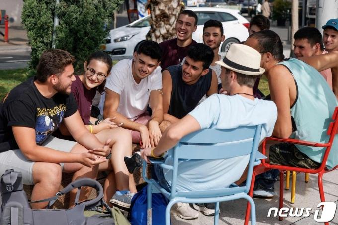 18일(현지시간) 야외에서 마스크 착용 의무 해제로 이스라엘 텔아비브 거리의 젊은이들이 '노 마스크' 상태로 대화를 하고 있다. © AFP=뉴스1 © News1 우동명 기자