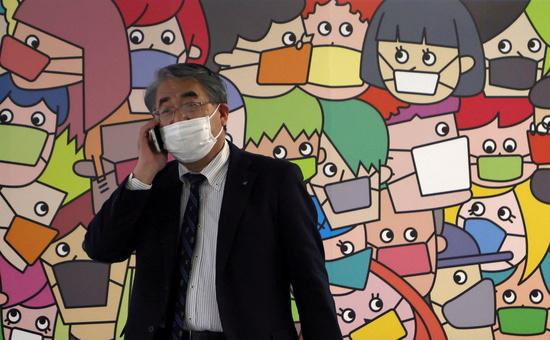 """일본에서 """"마스크를 쓰지 말고 피크닉을 가자""""는 제안이 sns를 통해 확산되고 있다. 사진은 일본 도쿄의 한 시민이 마스크를 착용한 채 통화하는 모습. /사진=로이터"""