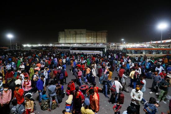 델리 정부가 19일 인도 뉴델리 외곽의 가지바드에서 코로나19 확산을 예방하기 위한 '6일 봉쇄령'을 내렸다. 이주노동자들이 버스 정류장에 모여 마을로 돌아가기 위해 버스에 오르고 있다./사진=로이터