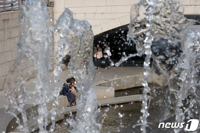 전국 대부분 지역에서 낮 기온이 20도 이상을 보인 20일 오후 서울 종로구 청계천에서 시원하게 뿜는 분수 너머로 시민들이 산책을 즐기고 있다. 2021.4.20/뉴스1 © News1 조태형 기자