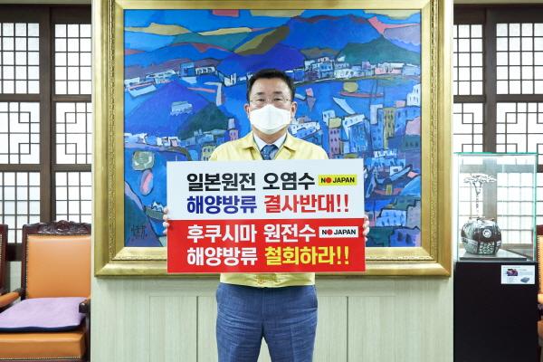 ▲강석주 통영시장이 오염수 방류 결정에 대한 규탄하는 피켓을 들고있다/사진=통영시