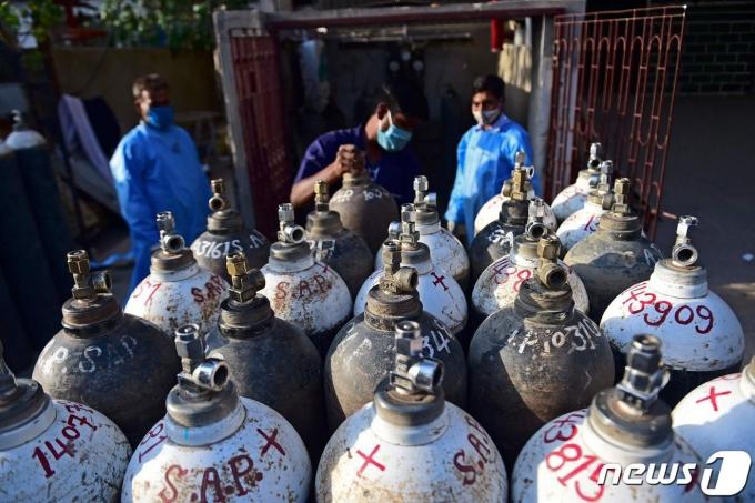 의료 관계자들이 인도 알라하바드의 한 병원에 있는 산소통들을 정리하고 있다. © AFP=뉴스1