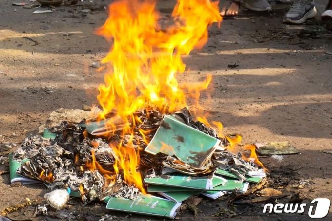 1일(현지시간) 군사 쿠데타를 반대하는 시위가 계속되는 미얀마 양곤에서 시민들이 2008년 헌법 책자를 불태우고 있다. © AFP=뉴스1 © News1 우동명 기자