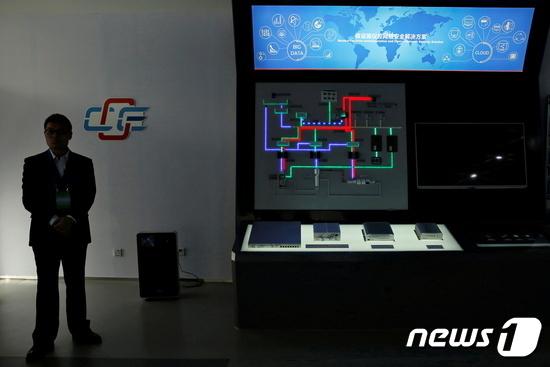 베이징 국가원자력보안기술센터 원자력보안 우수센터 전시장에서 한 직원이 원자력시설 계측제어 네트워크 보안 솔루션 전시장 옆에 서 있다. © 로이터=뉴스1
