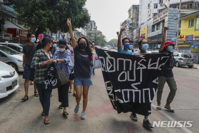 """지난 19일 미얀마 양곤에서 반 쿠데타 시위대가 """"혁명! 군사 정부의 노예로 살진 않겠다""""라고 쓰인 현수막을 들고 구호를 외치고 있다. /사진=뉴시스(양곤=AP)"""