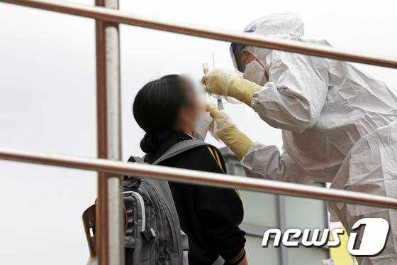 지난 22일 오후 광주 북구의 한 여자고등학교에서 의료진들이 학생과 교직원 등의 검체를 채취하고 있다. /사진=뉴스1