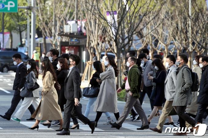 아침 기온이 떨어져 쌀쌀한 날씨를 보인 5일 서울 종로구 광화문 네거리에서 출근길 시민들이 발걸음을 옮기고 있다. 2021.4.5/뉴스1 © News1 이광호 기자