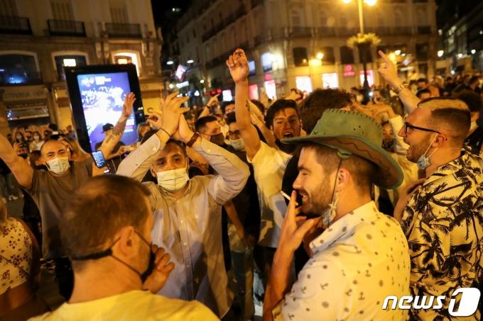 9일 스페인 마드리드 '푸에르타 델 솔' 광장에서 사람들이 환호하고 있다. © 로이터=뉴스1