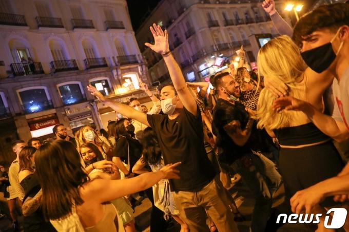 9일 스페인 마드리드 '푸에르타 델 솔' 광장에서 사람들이 환호하며 서로 껴안고 있다. © 로이터=뉴스1