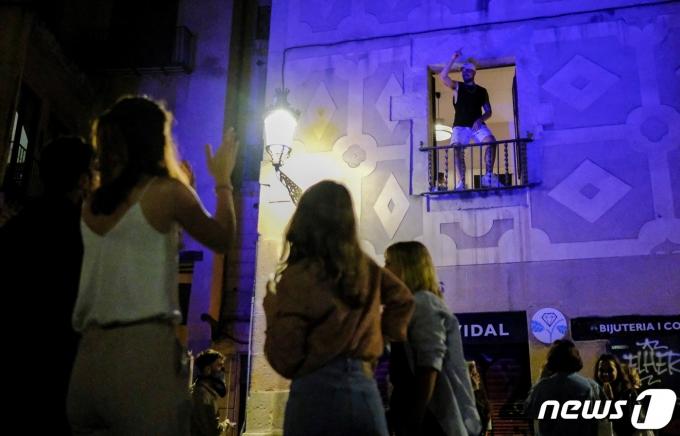 9일 스페인에서 야간 통행금지가 해제된 가운데 한 남성이 발코니에서 춤을 추고 있다. © 로이터=뉴스1