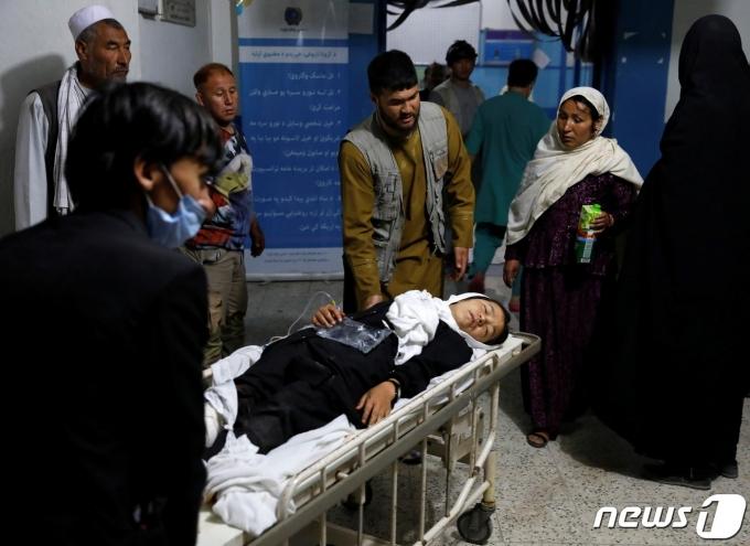 8일(현지시간) 아프가니스탄 수도 카불의 한 학교 근처에서 발생한 폭탄 테러로 부상한 여학생이 병원으로 이송되고 있다. © 로이터=뉴스1