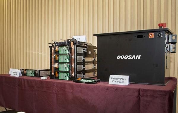두산인프라코어가 자체 개발한 배터리팩 시제품 1호기(오른쪽)와 셀 단위의 배터리를 일정한 개수로 묶어 프레임에 넣은 배터리모듈(왼쪽)이 전시돼 있다. /사진=두산인프라코어