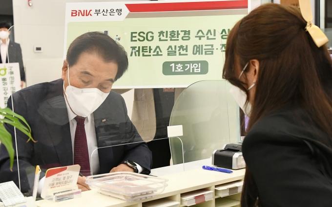 BNK김지완 회장은 11일 오전 본점 영업부를 방문해 '저탄소 실천 적금'을 1호로 가입했다./사진=부산은행