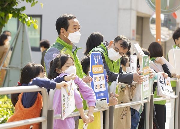 장희구 코오롱인더스트리 대표이사(왼쪽에서 세번째)가 11일 서울 강서구 가곡초등학교 앞 횡단보도에서 어린이 등굣길 교통지도 봉사활동을 하고 있다. /사진=코오롱