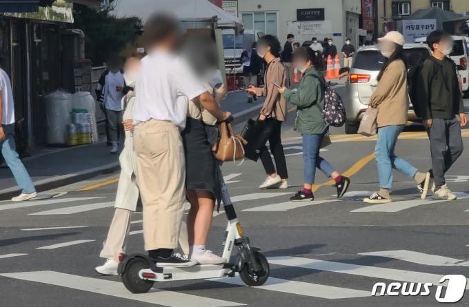 전동킥보드 등 개인형 이동장치(PM)의 이용 규제를 강화하는 개정 도로교통법 시행을 이틀 앞둔 11일 서울의 한 횡단보도에서 시민들이 전동킥보드에 동승하고 있다. 2021.5.11/뉴스1 © News1 허경 기자