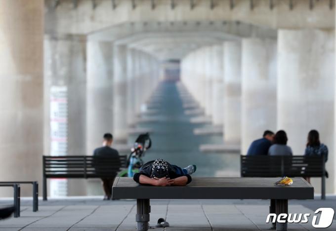 서울의 낮 기온이 28도까지 오르며 초여름 날씨를 보인 12일 오후 서울 여의도 한강공원을 찾은 시민들이 그늘 아래서 쉬고 있다. 2021.5.12/뉴스1 © News1 구윤성 기자