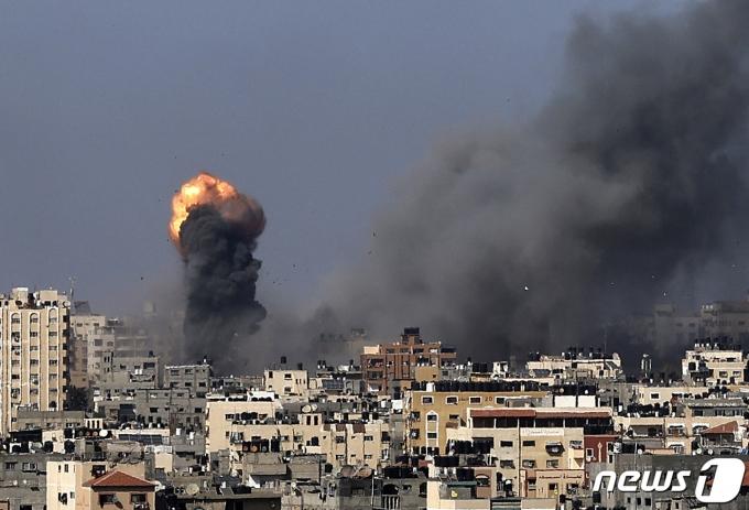 12일(현지시간) 팔레스타인 무장 정파 하마스가 지배하는 가자지구에서 이스라엘군의 공습으로 화염과 검은 연기가 치솟고 있다. © AFP=뉴스1 © News1 우동명 기자