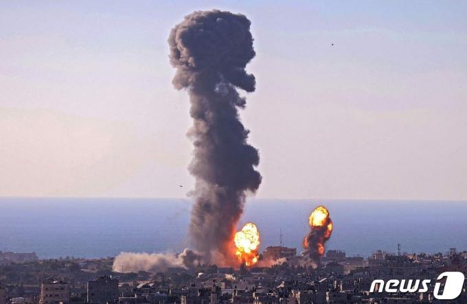 13일(현지시간) 팔레스타인 무장 정파 하마스가 지배하는 가자지구의 라파에서 이스라엘의 공습에 화염이 치솟고 있다. © AFP=뉴스1 © News1 우동명 기자