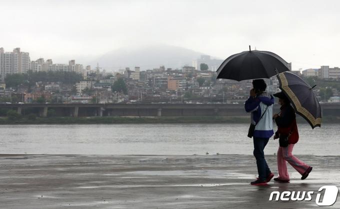 전국에 비가 내리고 있는 16일 서울 서초구 반포한강공원에서 우산을 쓴 시민들이 발걸음을 옮기고 있다. 기상청은 이날 중국 중부지방에서 발달해 서해상에서 발달해 동진하는 저기압의 영향을 받아 새벽부터 전국에 비가 내린다고 예보했다. 2021.5.16/뉴스1 © News1 박세연 기자