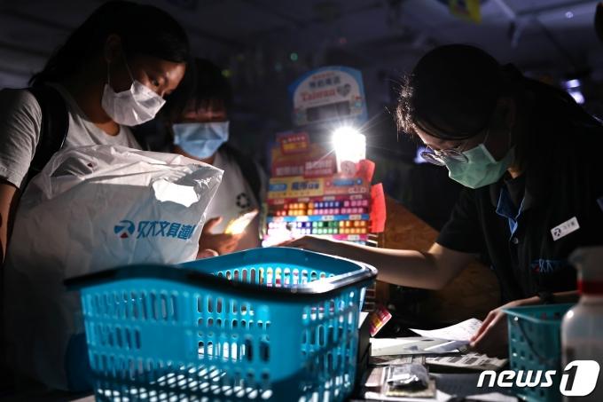 13일 대만 타이베이의 한 상점에서 손님들이 정전 사태로 인해 전구 불빛에 의존해 물건을 계산하고 있다. © 로이터=뉴스1