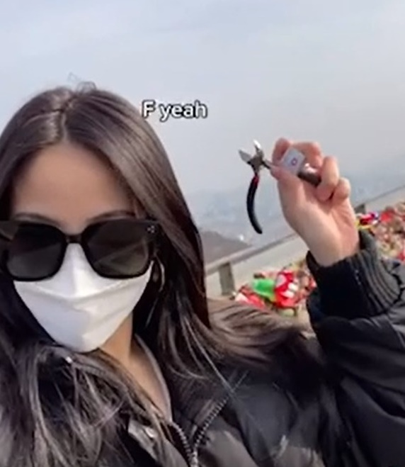 한 여성이 남산에 매달아 놓은 자물쇠를 자르는 영상을 올려 화제를 모았다./ 사진=틱톡 캡처