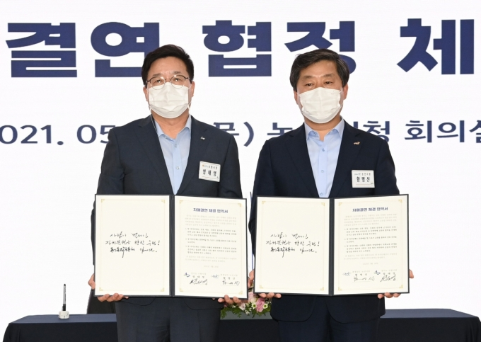 염태영 수원시장(왼쪽)과 황명선 논산시장이 협약서에 서명한 후 함께하고 있다. / 사진제공=수원시